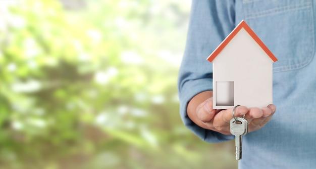 Agente inmobiliario entregando las llaves de la casa en la mano