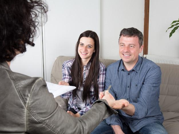Agente inmobiliario entregando las llaves de la casa a una pareja joven