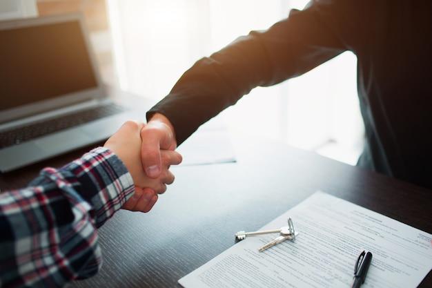 Agente inmobiliario estrechándole la mano al cliente después de la firma del contrato