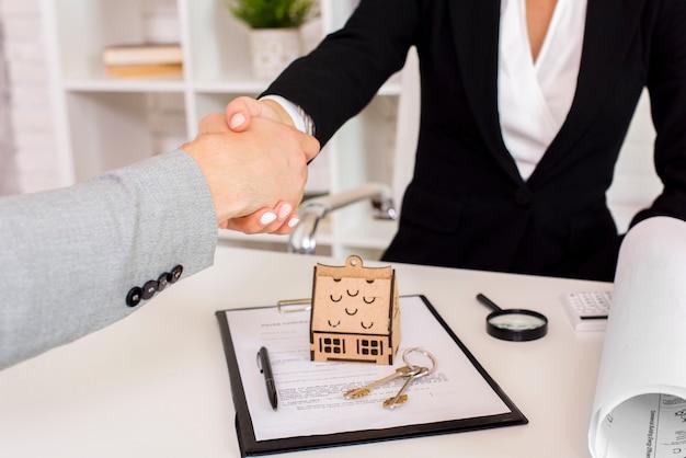 Agente inmobiliario estrechándole la mano al cliente