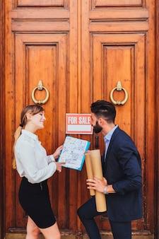 Agente inmobiliario feliz mostrando los planos