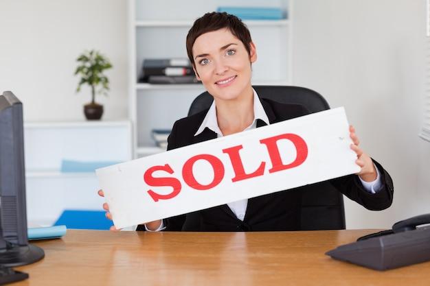 Agente inmobiliario feliz con un panel vendido.