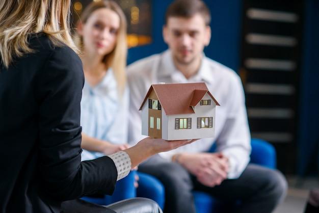 Agente inmobiliario femenino, diseñador de interiores que muestra el modelo 3d de la casa a la linda pareja caucásica.