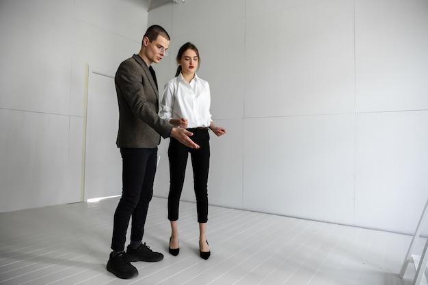 Agente inmobiliario femenino que muestra el nuevo hogar a un joven después de una discusión sobre los planes de la casa mudando el nuevo concepto de hogar Foto gratis