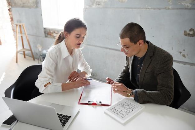 Agente inmobiliario femenino que muestra un nuevo hogar a un joven después de una discusión sobre los planos de la casa.