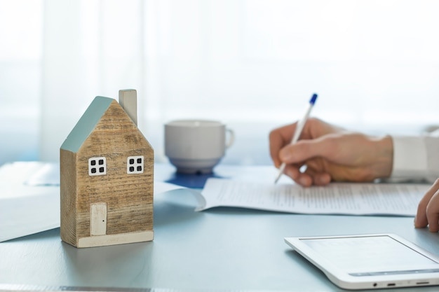 El agente inmobiliario firma la documentación de la transacción mientras. comprando una casa. hipoteca.