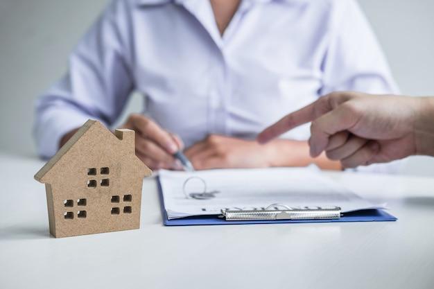 El agente inmobiliario llega a un formulario de contrato con el cliente que firma un contrato de bienes inmuebles