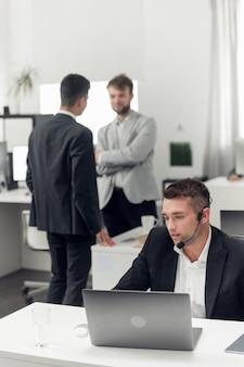 Un agente inmobiliario en el lugar de trabajo de la agencia negocia con el cliente a través de internet y por teléfono.
