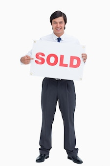 Agente inmobiliario masculino sonriente que señala en el cartel vendido