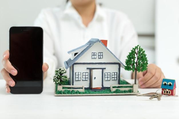 Agente inmobiliario con modelo de casa y teléfono