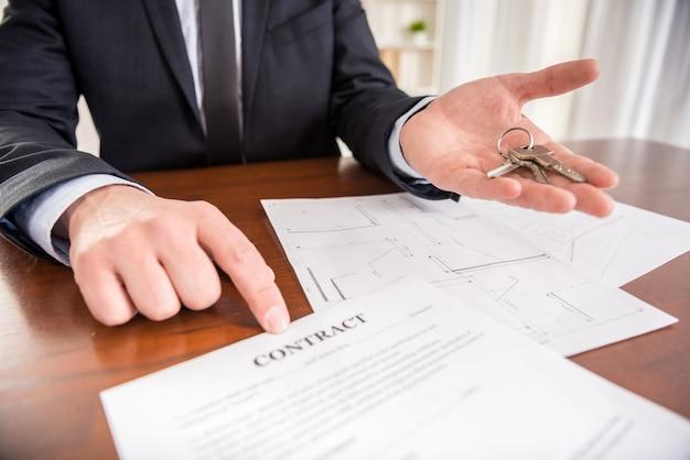 El agente inmobiliario está mostrando un contacto con la llave del apartamento nuevo.