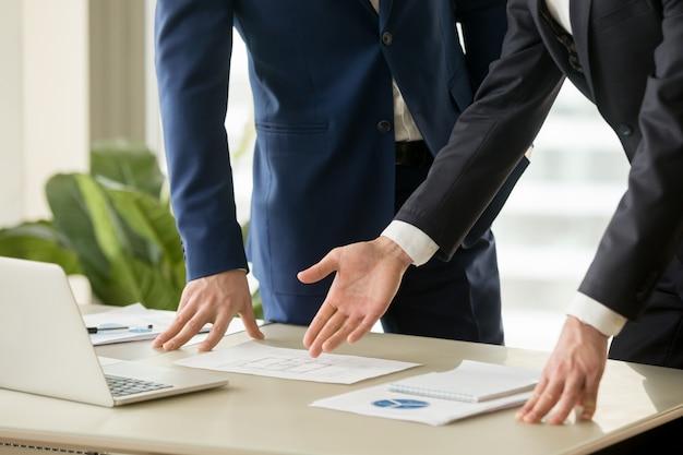 Agente inmobiliario mostrando el plan de la casa al comprador.