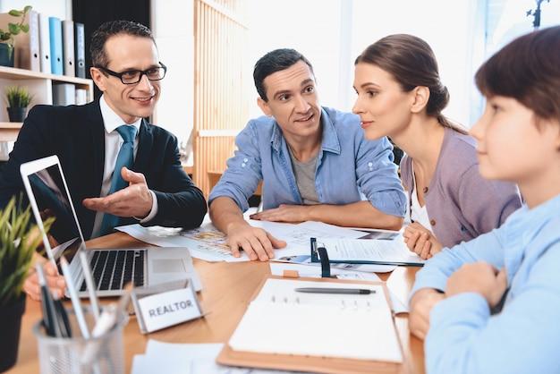 El agente inmobiliario está presentando la computadora portátil al padre, a la madre y al hijo.