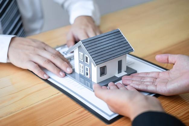 El agente inmobiliario está presentando un préstamo hipotecario y entregando la casa al cliente después de discutir y firmar el contrato de acuerdo con el formulario de solicitud aprobado, el seguro de hogar y el concepto de inversión inmobiliaria.