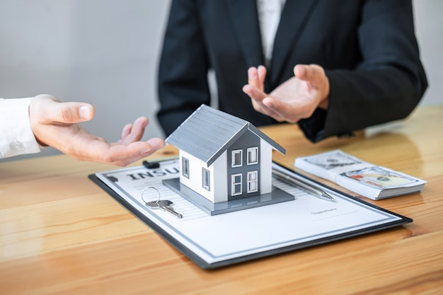 El agente inmobiliario está presentando un préstamo hipotecario y entregando la casa al cliente después de discutir y firmar un contrato con un formulario de solicitud aprobado