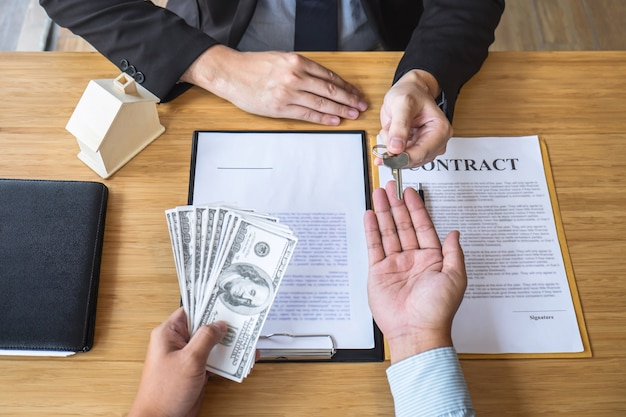 El agente inmobiliario está presentando el préstamo hipotecario y enviando las llaves al cliente después de firmar el contrato para comprar