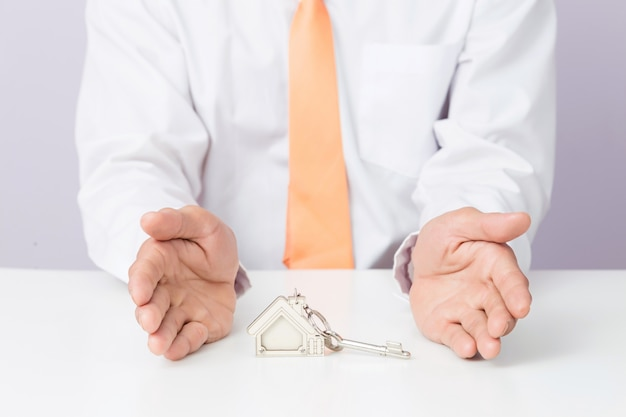 Agente inmobiliario que da las llaves de la casa, fondo aislado,
