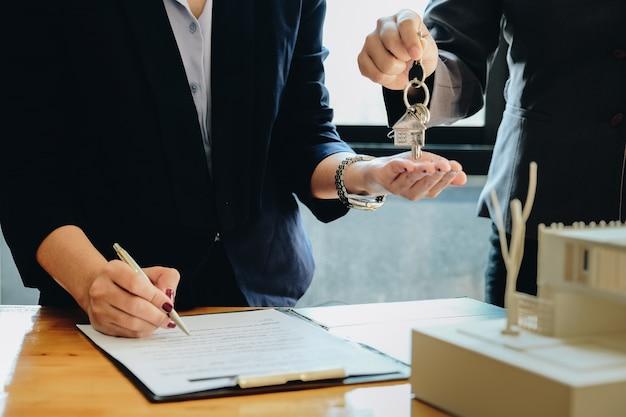 Agente inmobiliario que da las llaves de la casa a la mujer y firma un acuerdo en la oficina