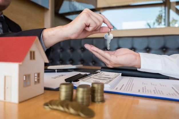 Agente inmobiliario que entrega la casa clave cliente firma acuerdo de propiedad