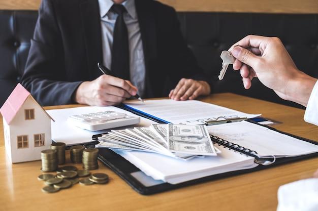 Agente inmobiliario que entrega las llaves de la casa al cliente después de firmar un contrato de bienes raíces con un formulario de solicitud de hipoteca aprobado, sobre la oferta de préstamo hipotecario y el seguro de la casa