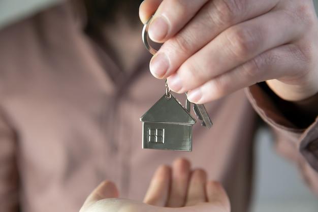 Agente inmobiliario que entrega las llaves de la casa al cliente para una nueva casa, contrato de bienes raíces para hipoteca aprobada, enfoque en llaves, negocios, finanzas, bienes