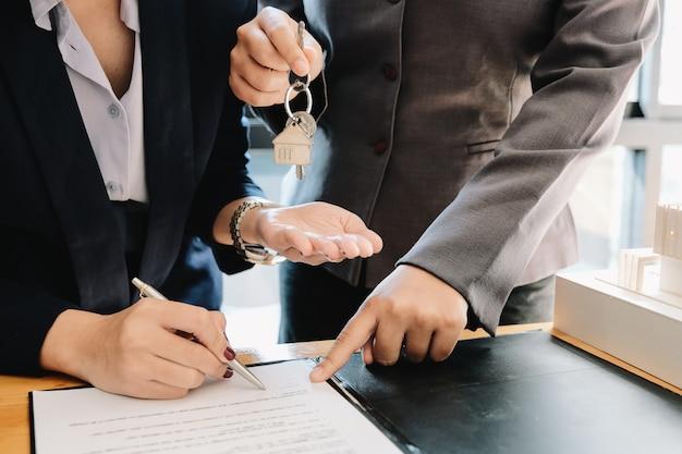 Agente inmobiliario que entrega las llaves de la casa al hombre y firma un acuerdo en la oficina
