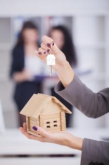 Agente inmobiliario que entrega las llaves de la casa a un cliente