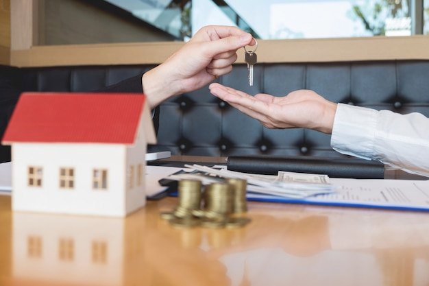Agente inmobiliario que entrega las llaves de la casa. firma del acuerdo.