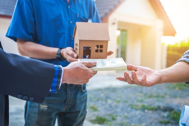 Agente inmobiliario que entrega las llaves de la casa frente al stand de la casa con el arquitecto