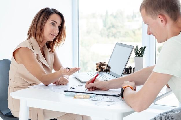 Agente inmobiliario que entrega las llaves de la nueva casa de una pareja