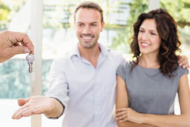 Agente inmobiliario que entrega llaves a nuevos propietarios