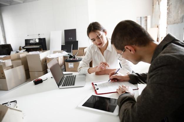 Agente inmobiliario que muestra un nuevo hogar a un joven después de una discusión sobre los planes de la casa, el concepto de mudanza y el nuevo hogar