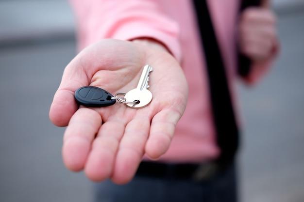 Agente inmobiliario que ofrece las llaves de la casa nueva mano closeup