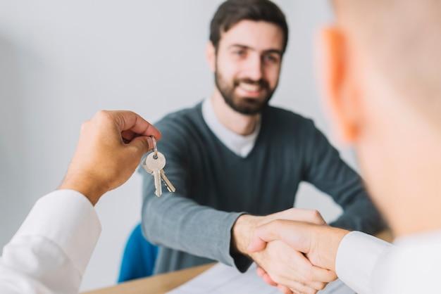 Agente inmobiliario que sacude la mano del cliente y que sostiene llaves