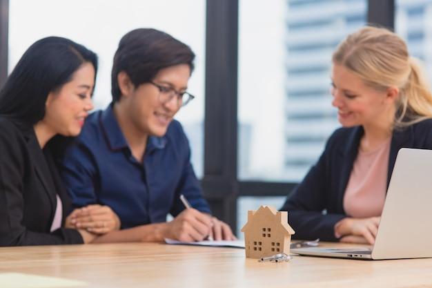 Agente inmobiliario en una reunión con pareja asiática