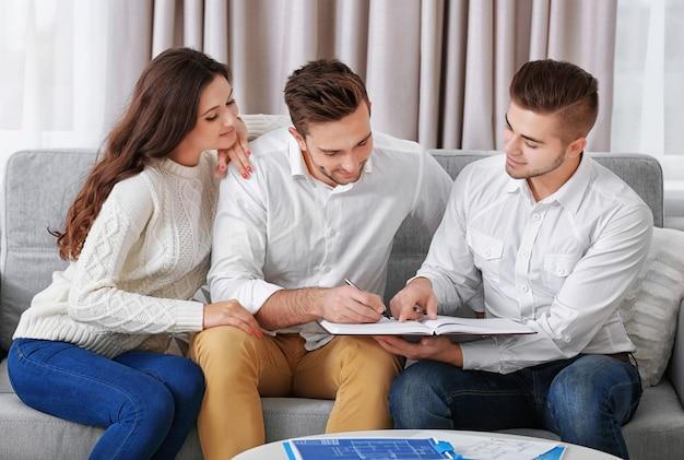 Agente inmobiliario reunión con pareja feliz, a la luz