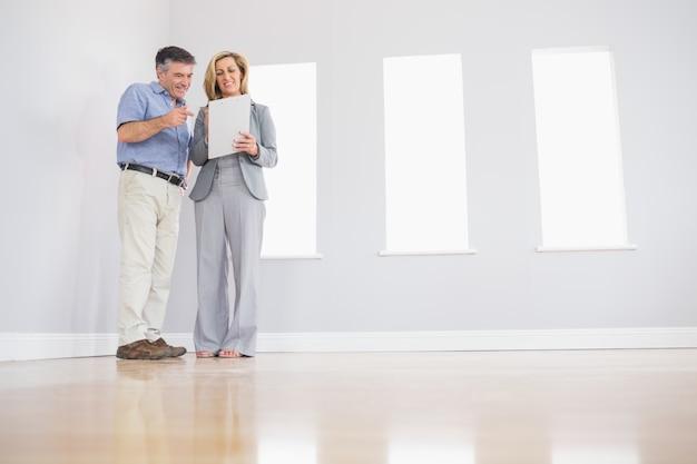 Agente inmobiliario rubio alegre que muestra una habitación y algunos documentos a un comprador atento potencial