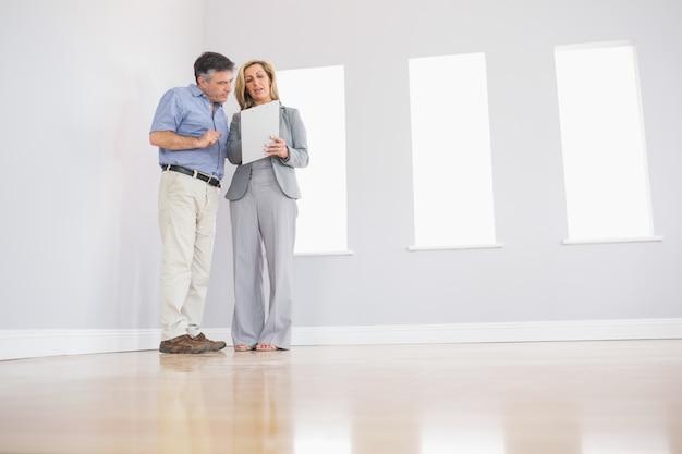 Agente inmobiliario rubio concentrado que muestra una habitación y algunos documentos a un potencial comprador atento