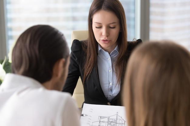 Agente inmobiliario serio femenino que discute plan de la construcción de viviendas con los clientes