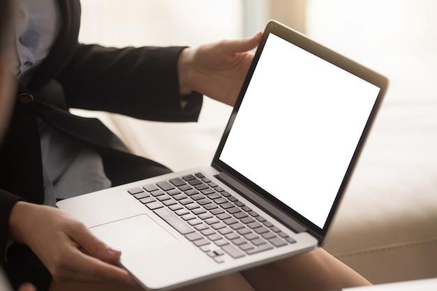 Agente inmobiliario de sexo femenino que muestra plan de la casa en la pantalla del ordenador portátil