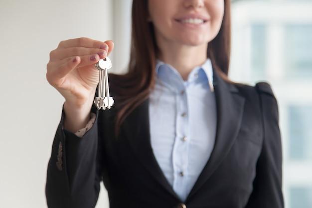 Agente inmobiliario de sexo femenino que sostiene llaves, concepto de compra de compra de propiedad