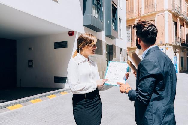 Agente inmobiliario sonriente hablando con el arquitecto