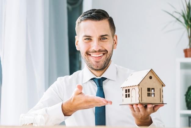 Agente inmobiliario sonriente que demuestra la casa de juguete