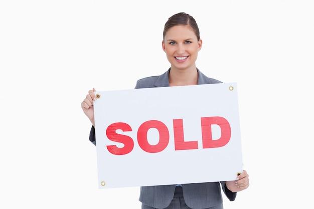 Agente inmobiliario sonriente que presenta el cartel vendido