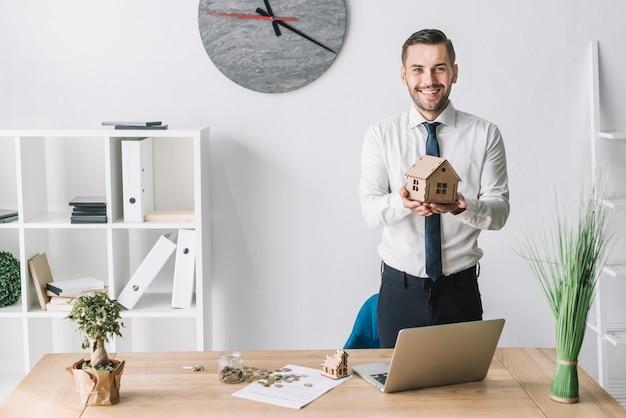 Agente inmobiliario sonriente que sostiene la casa