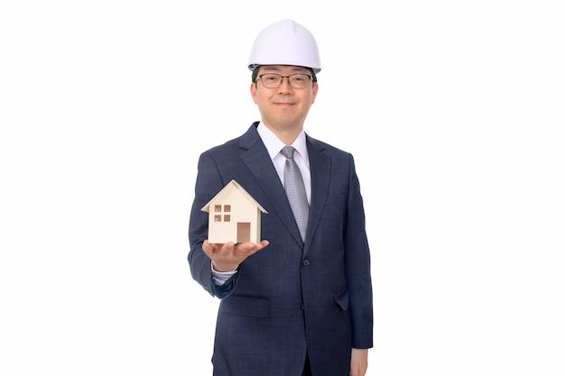 Agente inmobiliario sosteniendo una casa de juguete