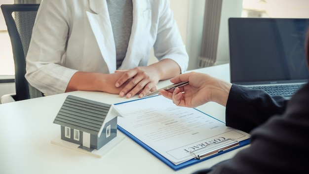 El agente inmobiliario sostiene un bolígrafo y explica el contrato comercial a la clienta.