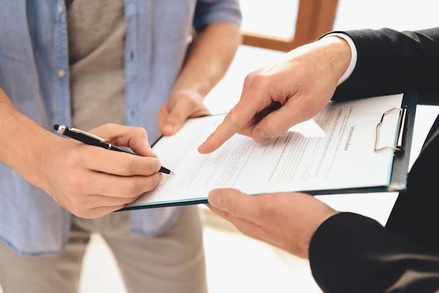 El agente inmobiliario sostiene una tableta y un hombre firma.
