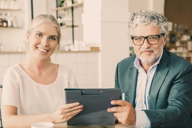 Agente joven y cliente maduro reunido sobre una taza de café en el coworking, sentado a la mesa, sosteniendo documentos