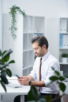 Agente joven en ropa formal sentado junto al escritorio mientras se desplaza por los contactos de sus clientes en el teléfono inteligente